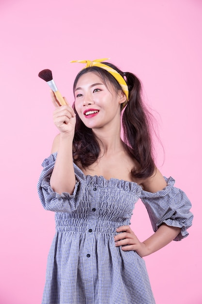 Beautiful woman holding a brush, brushed on a pink background. Free Photo