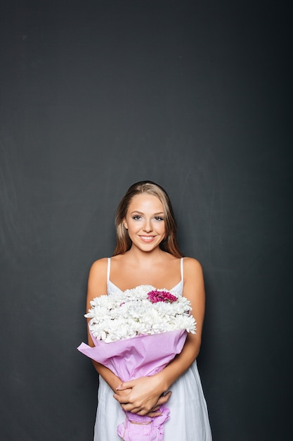 Beautiful woman holding bunch of flowers Free Photo