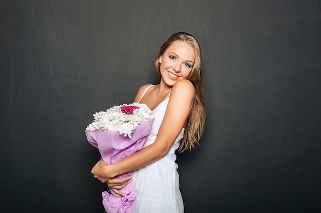 Beautiful woman holding bunch of flowers Free Photo
