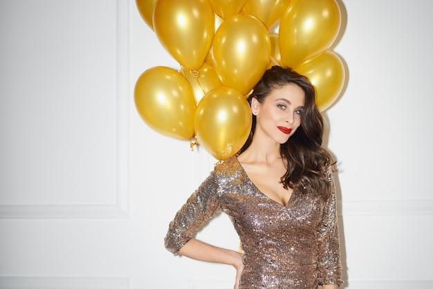 金色の風船の束を保持している美しい女性 無料写真