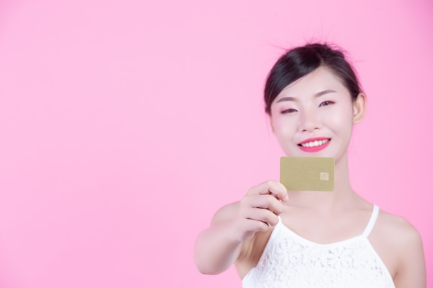 Beautiful woman holding a card on a pink background. Free Photo