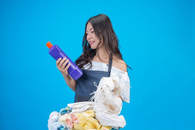 A beautiful woman holding a cloth and liquid detergent prepared for washing on blue Free Photo