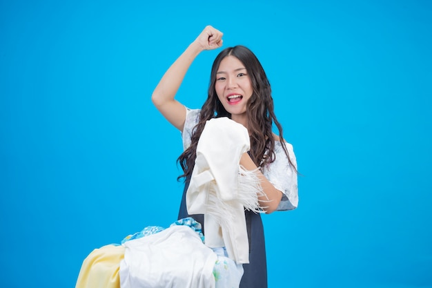 A beautiful woman holding a cloth prepared to wash on blue Free Photo