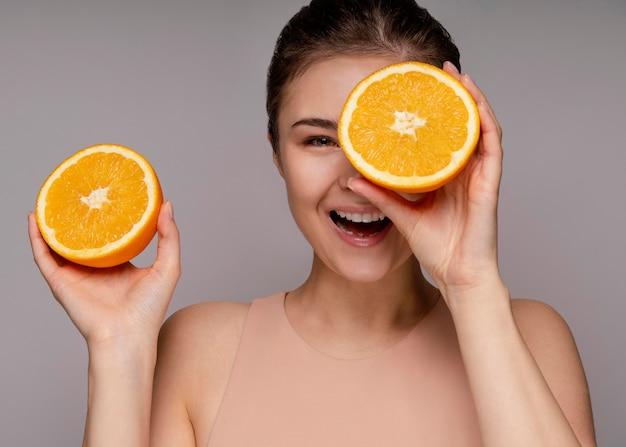 Красивая женщина, держащая половину апельсина Бесплатные Фотографии