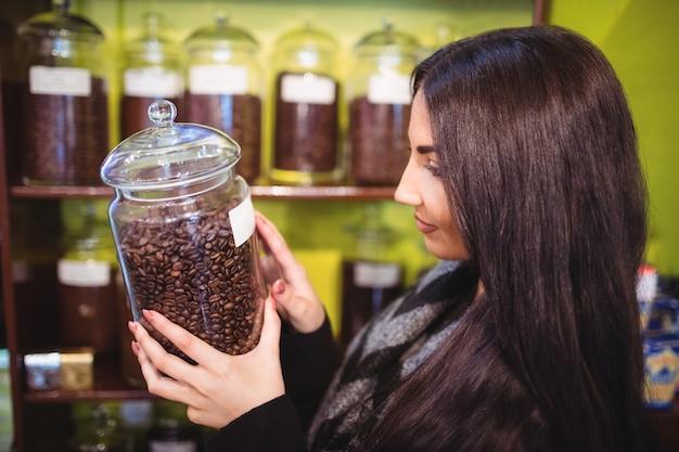 Bella donna che tiene un barattolo di chicchi di caffè Foto Gratuite