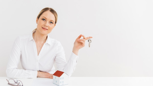 Beautiful woman holding keys looking at camera Free Photo