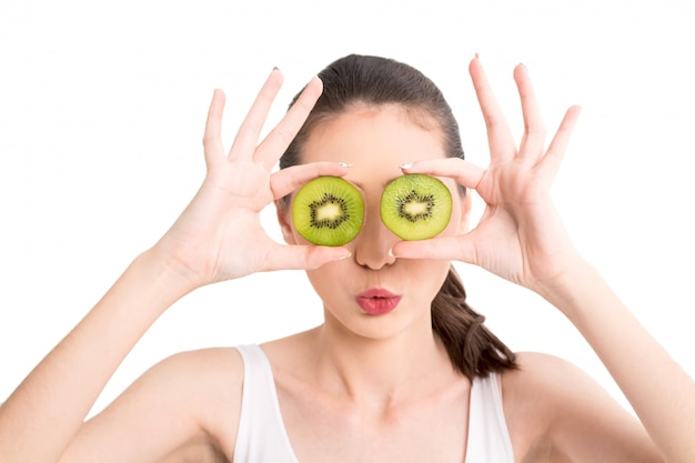 Beautiful woman holding kiwi slice hiding eye behind isolated on white background Premium Photo