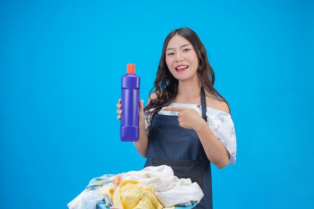 Beautiful woman holding laundry detergent prepared on blue Free Photo