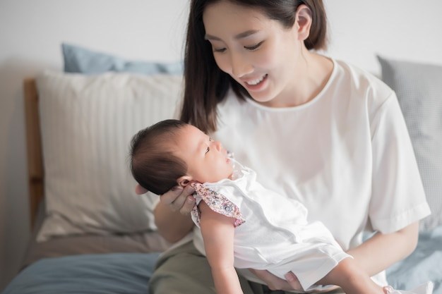 Beautiful woman holding a newborn baby in her arms Premium Photo