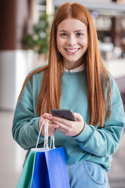 Beautiful woman holding phone and paper bags Free Photo