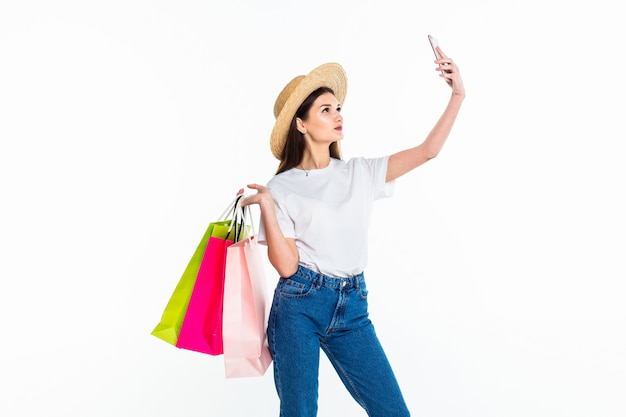 Beautiful woman holding shopping bags and taking selfie with cell phone isolated on white wall Free Photo