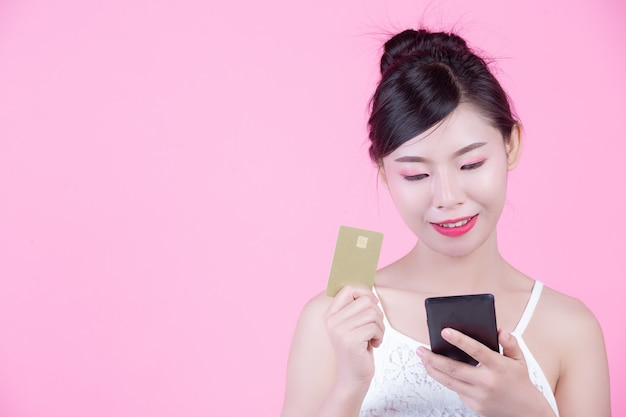 Beautiful woman holding a smartphone and card on a pink background Free Photo