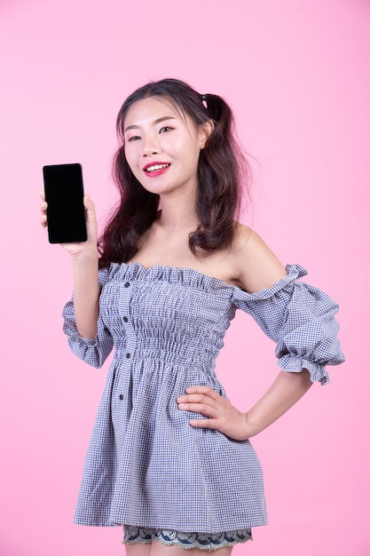 Beautiful woman holding a smartphone on a pink background. Free Photo
