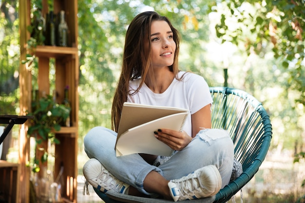 Beautiful woman holding a textbook while sitting in a chair Free Photo