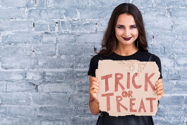 Beautiful woman holding trick or treat sign Free Photo