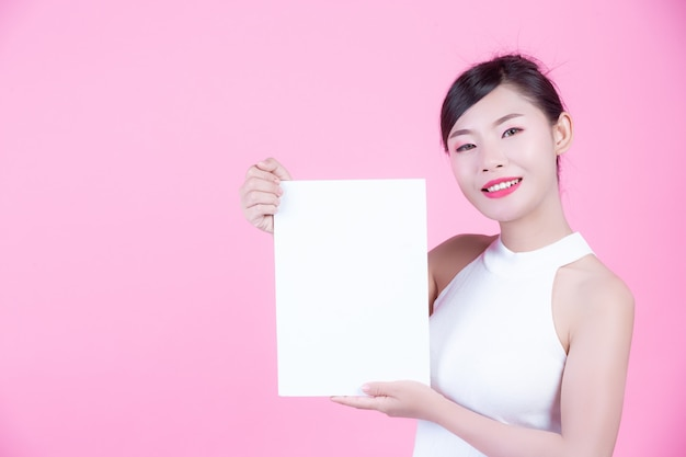 Beautiful woman holding a white board sheet on a pink background. Free Photo