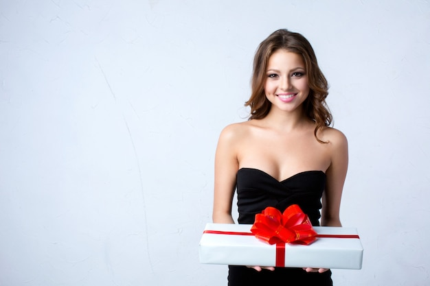Beautiful woman holding a white gift box with red ribbon. Premium Photo