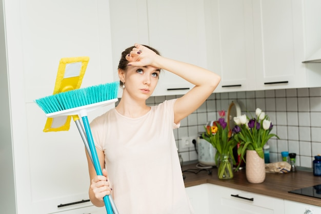 A beautiful woman holds a mop and brush for cleaning in her hands and sighs of fatigue Premium Photo
