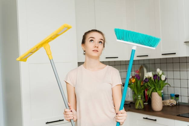 A beautiful woman holds a mop and brush for cleaning and mopping in her hands and sighs of fatigue. a housewife stands in the kitchen and wipes sweat from her face Premium Photo
