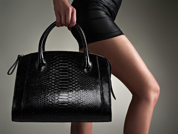 Piękna kobieta trzyma stylową czarną torbę.  modna dziewczyna.  stylowa koncepcja glamour.  sztuka.  kobieta po zakupach.  nierozpoznawalna kobieta.  Darmowe zdjęcie