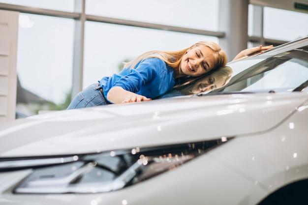 車のショールームで車を抱いて美しい女性 無料写真