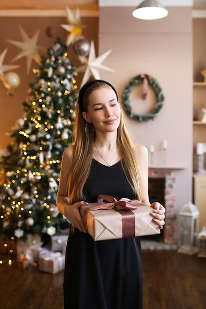 クリスマスツリーの近くに彼女の手でギフトを黒のドレスで美しい女性 Premium写真