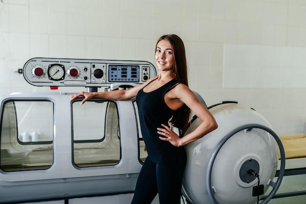 Красивая женщина в черной футболке и белых штанах лежит в гипербарической камере Premium Фотографии