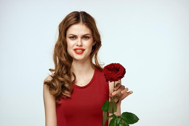 赤いドレスを着た美しい女性は、彼女の手にバラを持って、ギフトの花の装飾の魅力的な外観です。 Premium写真