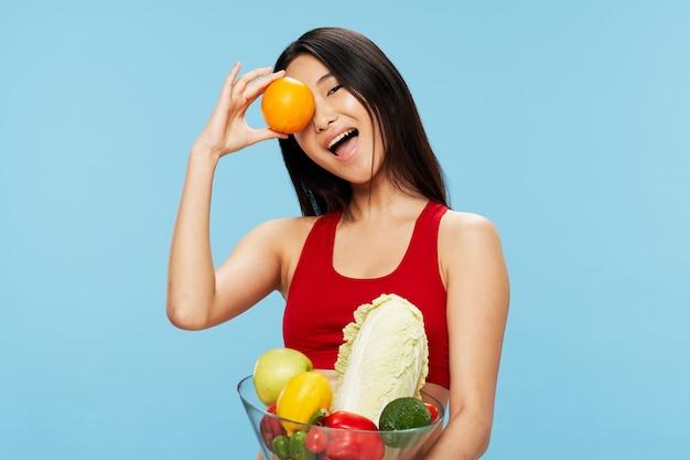 新鮮な野菜や果物の赤いタンクトップで美しい女性 Premium写真