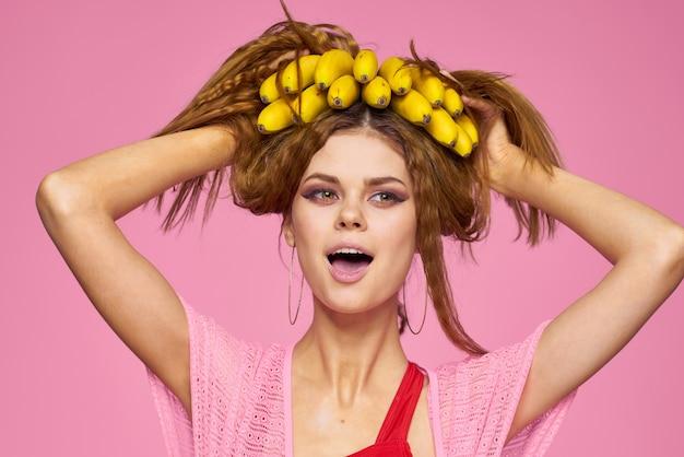 麦わら帽子とピンクの背景にバナナを手に、熱帯のヤシの木でポーズの水着で美しい女性 Premium写真
