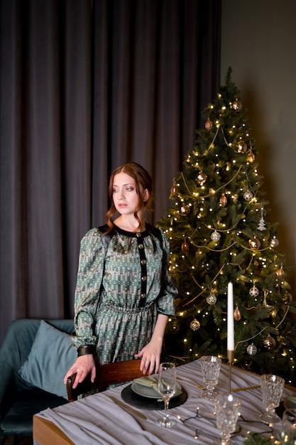 部屋の豊かなインテリアの豪華なクリスマスツリーの背景に黒のエレガントなドレスの美しい女性 Premium写真