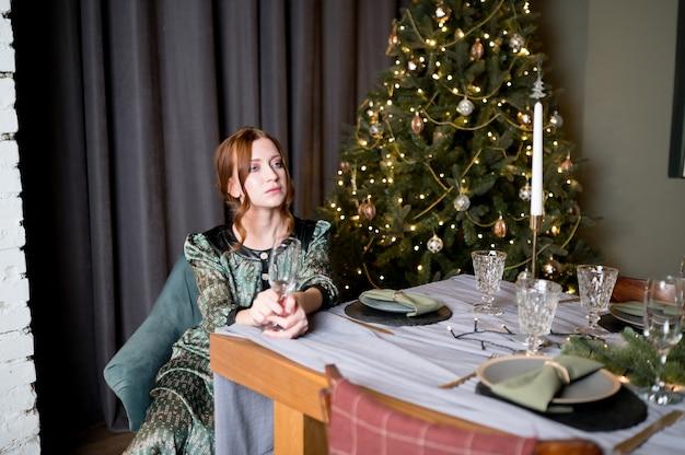 部屋の豊かなインテリアで豪華なクリスマスツリーを背景にエレガントなドレスの美しい女性 Premium写真