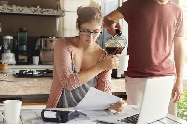 Красивая женщина в очках, держа лист бумаги, делая документы и платя налоги за кухонным столом с портативным компьютером и калькулятором на нем. ее муж стоит рядом и наливает кофе ей в кружку Бесплатные Фотографии