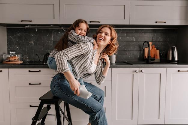 彼女の娘が後ろから彼女を抱きしめている間、ジーンズの美しい女性は台所の椅子に座っています。 無料写真
