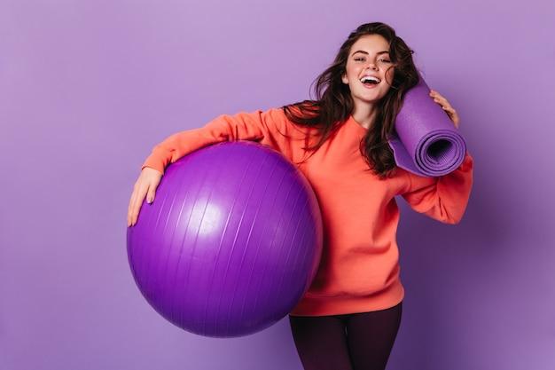 レギンスと明るいスウェットシャツの美しい女性は笑顔で紫色のマットとフィットボールでポーズをとっています 無料写真
