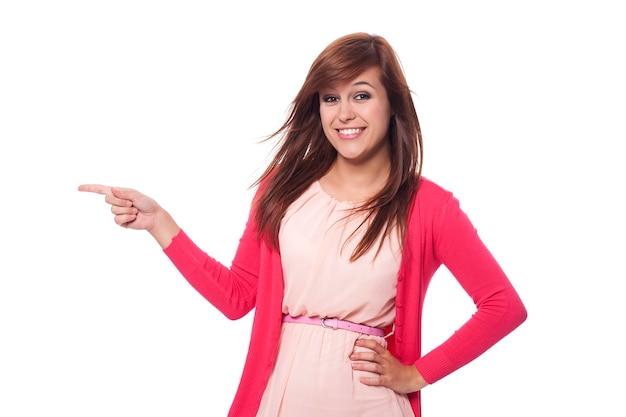 Красивая женщина в розовой одежде, указывая на копию пространства Бесплатные Фотографии