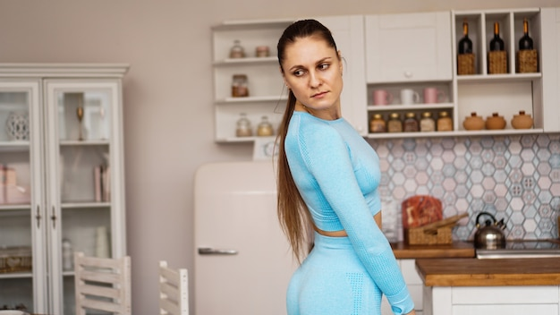 스포츠 유니폼에서 아름 다운 여자는 집에서 스포츠 훈련을 위해 준비 중입니다. 프리미엄 사진