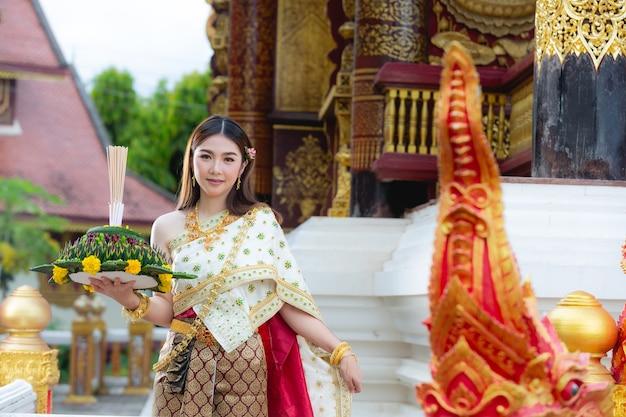 笑顔で寺院に立っているタイの伝統的な衣装の美しい女性 無料写真