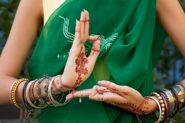 ヘナタトゥージュエリーとブレスレットと伝統的なイスラム教徒のインドの結婚式の緑のサリードレス衣装で美しい女性は手nritta odissi samyuta hastasダンス運動araalaコンセプトの背景 Premium写真