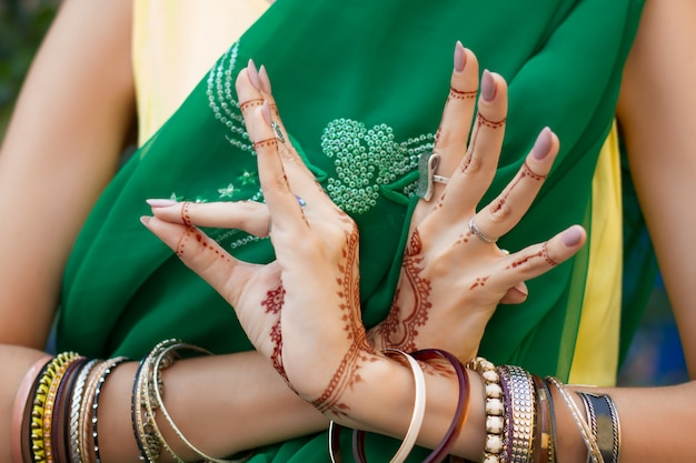 ヘナタトゥージュエリーブレスレットと伝統的なイスラム教徒のインドの結婚式グリーンサリードレス衣装で美しい女性は手nritta odissi samyuta hasta mudrasダンス運動鳥コンセプト背景 Premium写真