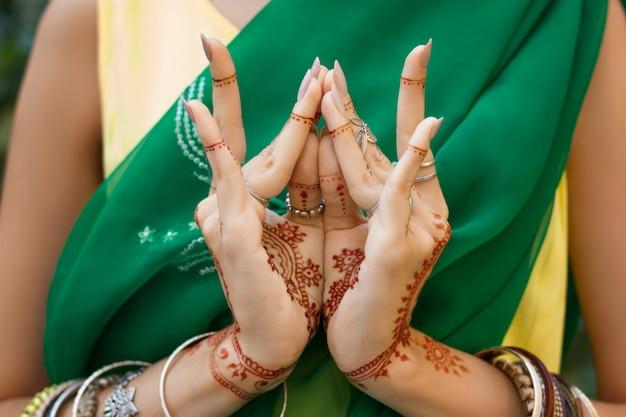 ヘナタトゥージュエリーブレスレットと伝統的なイスラム教徒のインドの結婚式の緑のサリードレスで美しい女性は手nritta odissi samyuta hasta mudrasダンス運動蓮のつぼみの花の概念の背景 Premium写真
