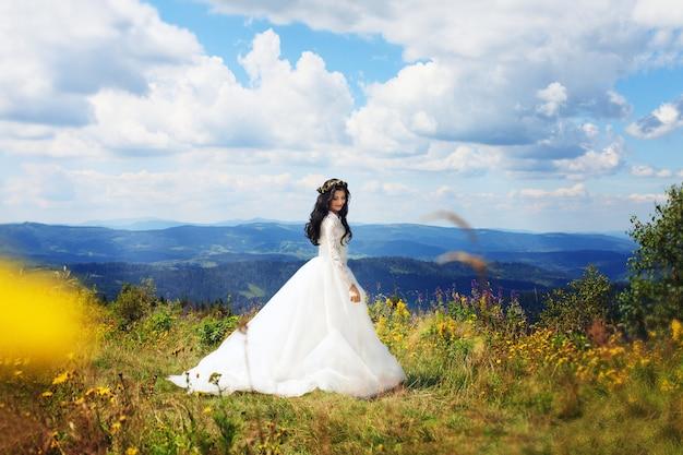 Красивая женщина в свадебном платье позирует в горах. предсвадебная фотосессия Premium Фотографии