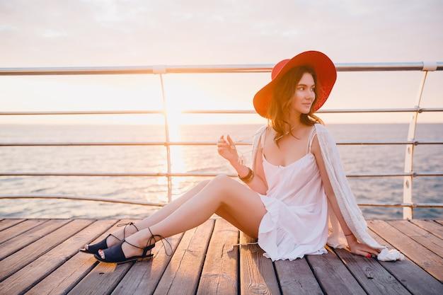 赤い帽子をかぶっているロマンチックな気分で日の出の海のそばに座っている白いドレスで美しい女性 無料写真
