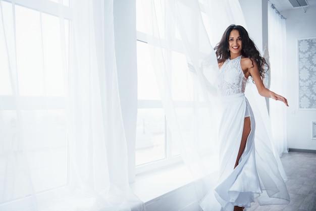 Красивая женщина в белом платье стоит в белой комнате с дневным светом через окна Бесплатные Фотографии