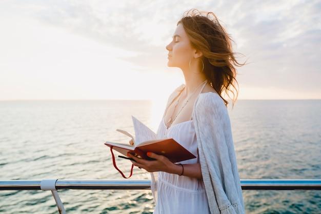ロマンチックな気分で日記の本を考えてノートを作って日の出に海沿いを歩く白い夏のドレスで美しい女性 無料写真
