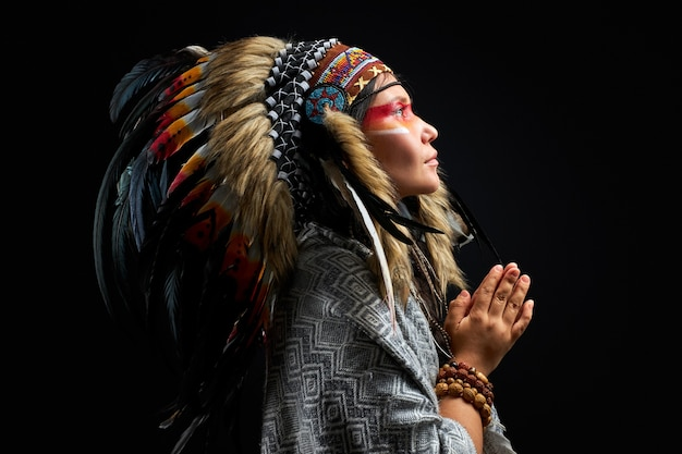 Beautiful woman in indian hat with feathers, accessories bohemians and boho, she is looking up, praying. isolated black wall Premium Photo