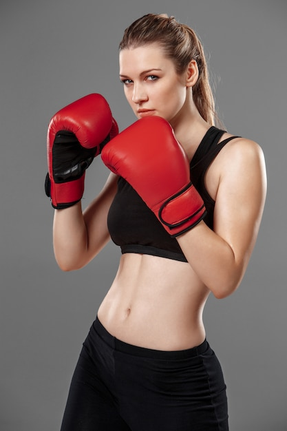 Beautiful woman is boxing on gray background Free Photo
