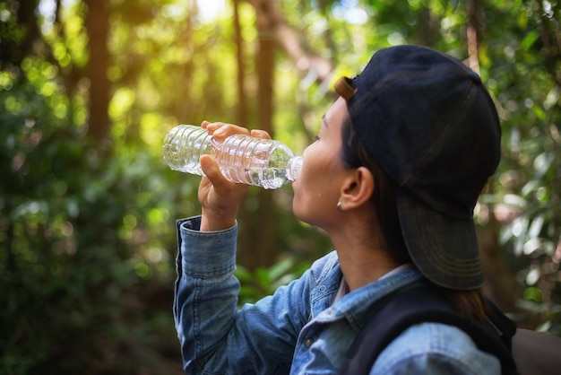 Beautiful woman is drinking water thirsty while hiking to travel Premium Photo