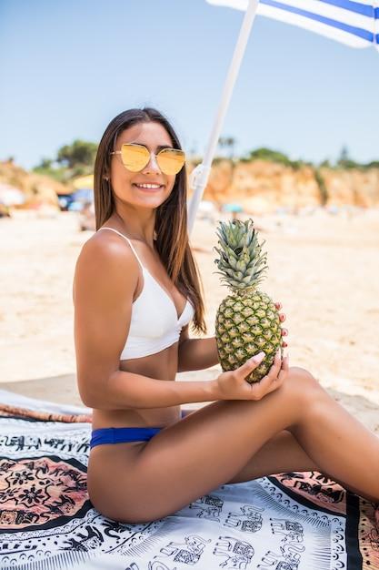 美しい女性はビーチでパイナップルフルーツを保持しています。 無料写真