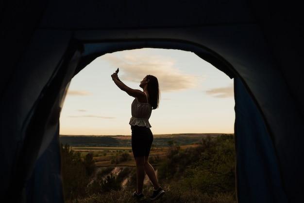 朝、山を背景にテントの近くで携帯電話を持ってセルフィーを撮っている美女。 Premium写真